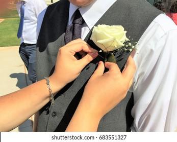 Woman pinning corsage on groomsman's tuxedo vest at wedding