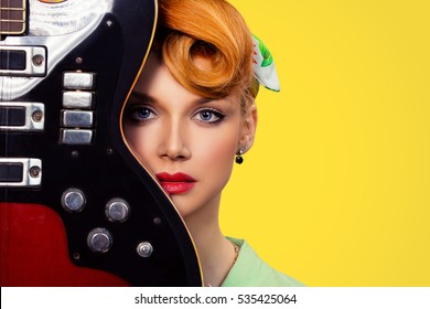 Woman pinup girl with electric acoustic rock guitar isolated yellow background