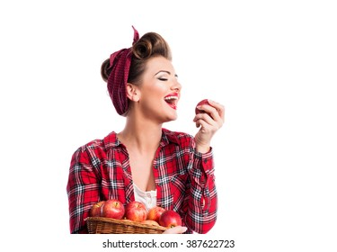 Woman, pin-up hairstyle holding basket, eating apple. Autumn har