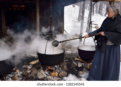 Woman in pioneer clothes ladling evaporated sap in cast iron pots to produce maple syrup Kortright Centre for Conservation,  Woodbridge, Ontario, Canada - March 1, 2015