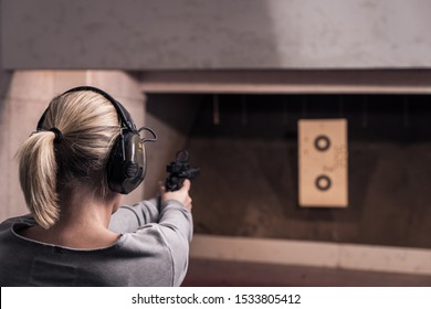 Woman with pistol weapon in hands at shooting range with target