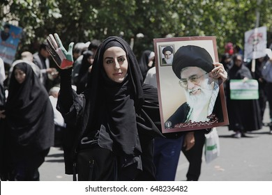 A woman with a placard Ali Khamenei on Qods Day protests, Tehran, Iran, July 10, 2015.