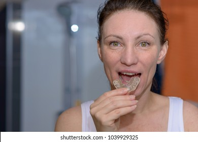 Woman placing a bite plate in her mouth to protect her teeth at night from grinding caused by bruxism, close up view of her hand and the appliance