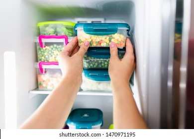 Woman placing container with frozen mixed vegetables in freezer.