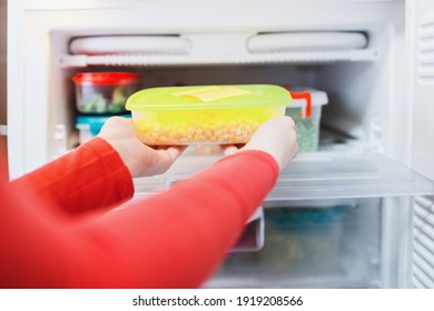 Woman placing containers with frozen vegetables in freezer.