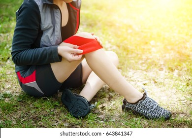 Woman placing kinesiology tape on knee. To prevent injuries.