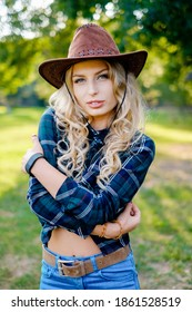 Woman in plaid shirt and cowboy hat. Smilng pretty young cowgirl.