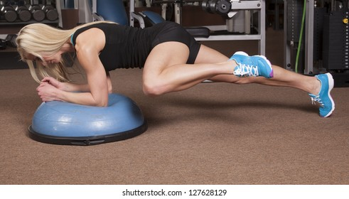 a woman in plank on a half of a ball bringing her knee to her arm.