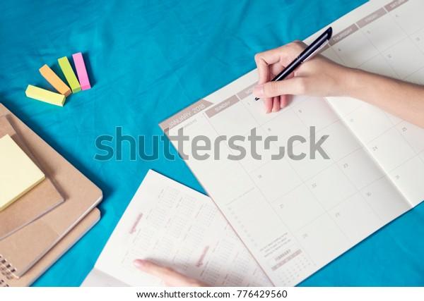 La mujer planifica la agenda y el programa usando el planificador de eventos del calendario, escribiendo el plan en el programa de memo. Las mujeres usan el plan de vacaciones para Feliz Año Nuevo 2018.