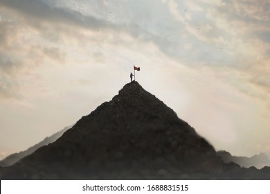 woman plants his flag on the mountain peak as a sign of success