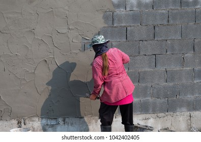 woman  plasterer concrete worker at the fence of house construction