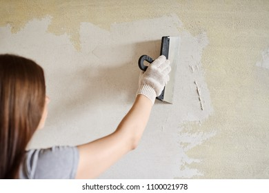 Woman plastering the walls with finishing putty in the room with putty knife or spatula. Repair work, decoration building concept, construction.