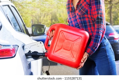 Woman with plastic canister filling car tank