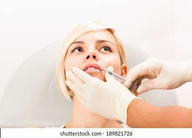 woman plastic surgery clinic, doctor hand in glove hold feamle face make botox injection in lips, cosmetic hospital medical beauty