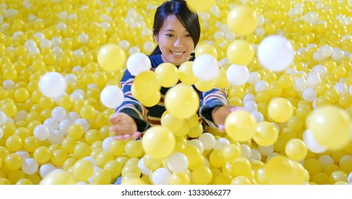 Woman play inside the ball pit