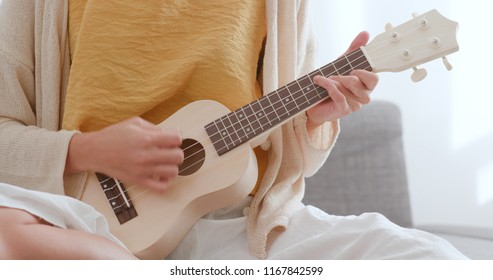 Woman play a song on ukulele