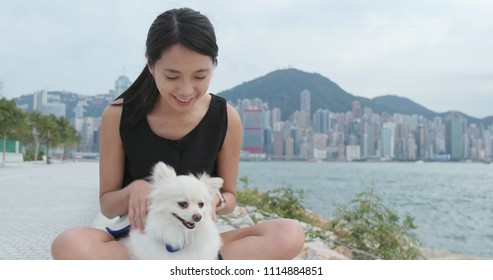 Woman play with white pomeranian dog at outdoor