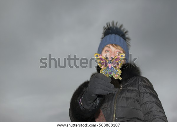 Woman in a playful mood covering her face with a plastic butterfly against the dark sky.