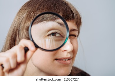 A woman playfully looking through a magnifying glass. On a gray background.