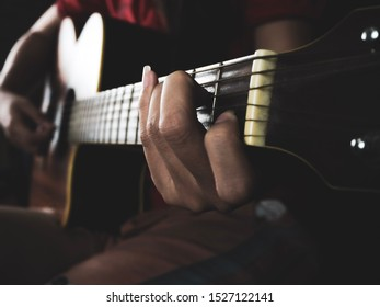 Woman playing acoustic guitar focusing on hand holding C major chords
