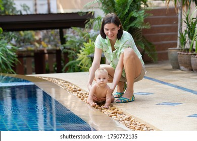Woman playing with baby near the pool
