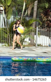 A woman is playing with a beachball next to a pool.  She is running with the ball and looking away from the camera.  Vertically framed photo.