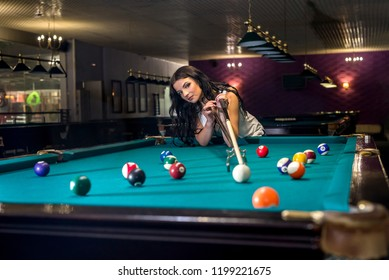 Woman playing billiard and using bridge rack