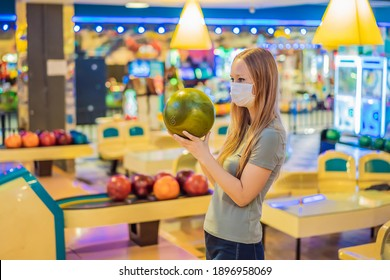 Woman playing bowling with medical masks during COVID-19 coronavirus in bowling club