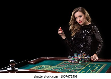 Woman playing in casino. Woman stakes piles of chips playing rou
