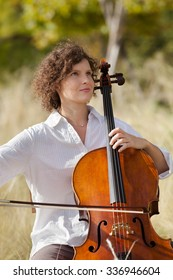 woman playing the cello between fields