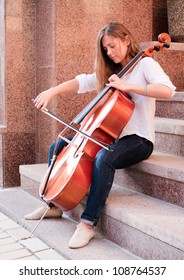 Woman playing cello on the stairway outdoors on street