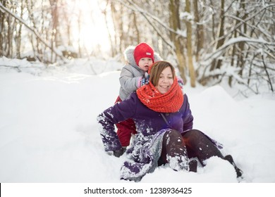 Woman playing with a child in the snow in the forest
