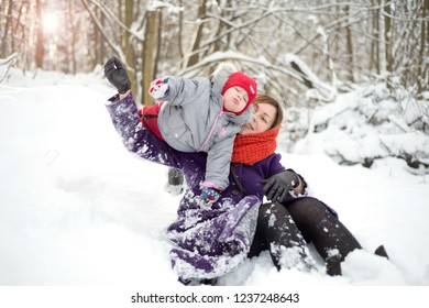 Woman playing with a child in the snow in the park