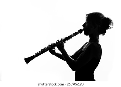 Woman playing the clarinet in silhouette