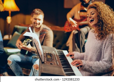 Woman playing clavier. Selective focus on woman. Home studio interior.