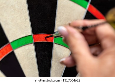 Woman playing dart, professional steeldart sport, closeup dartboard and dart point