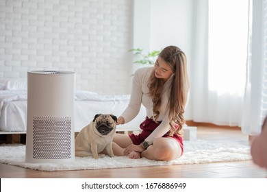 Woman playing with Dog Pug Breed and Air purifier in cozy white bed room for filter and cleaning removing dust PM2.5 HEPA in home,for fresh air and healthy life,Air Pollution Concept