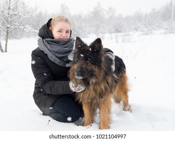 Woman playing with dog shepherd dog in the snow in winter