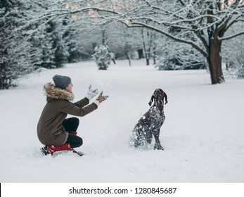 Woman playing with dog in snow