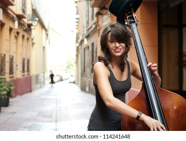 Woman playing double bass on the street  of european city