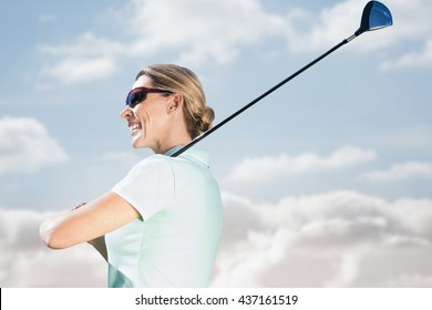 Woman playing golf against cloudy sky