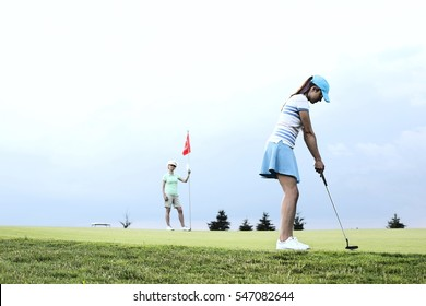 Woman playing golf with female friend against sky