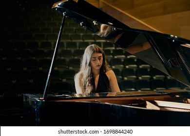 A woman playing a grand piano dressed in a black dress and her face is reflected in the open piano lid