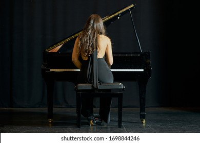 A woman playing a grand piano on a stage. Back view with black dress