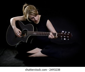 Woman playing guitar in a dark moody environment