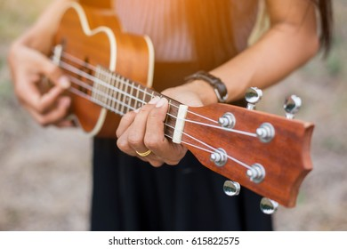 woman playing the  guitar in field