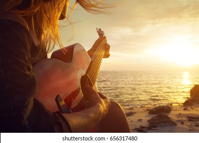 Woman playing guitar on sunset beach