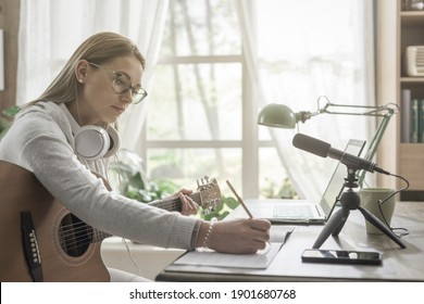Woman playing guitar and recording her music at home, she is using her laptop and a microphone