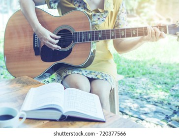 A woman is playing guitar and sing a song from Christian hymn  book with a cup of coffee on wooden table over garden background