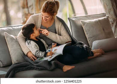 Woman playing with her son sitting on sofa with book. Mother and son having fun while reading a storybook at home. Woman touching nose of her son with book.